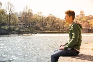 Contemplative teenage boy sitting beside river